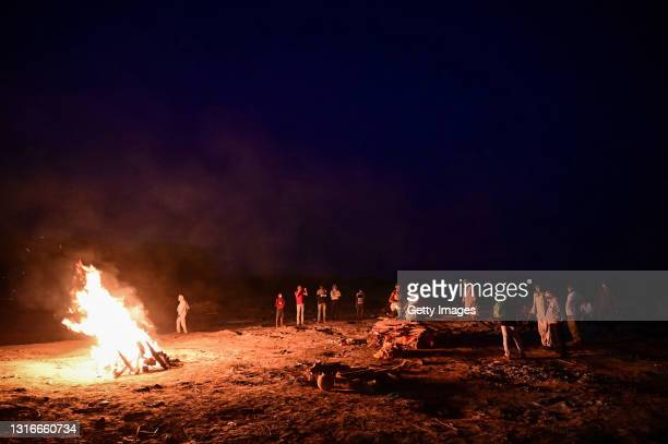 Worker helps cremate the bodies of Covid-19 victims on the banks of the Ganges river May 06, 2021 in Allahabad, Uttar Pradesh, India. India broke a...