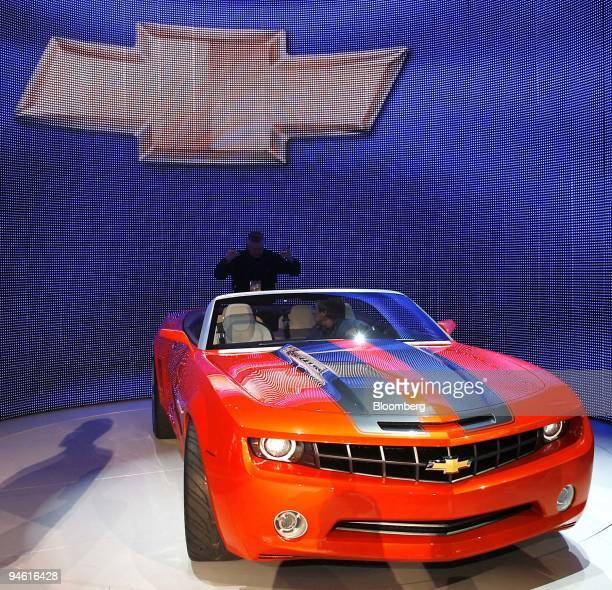 A worker helps guide the new Chevy Camaro convertible concept vehicle into place during the 2007 North American International Auto Show Detroit...