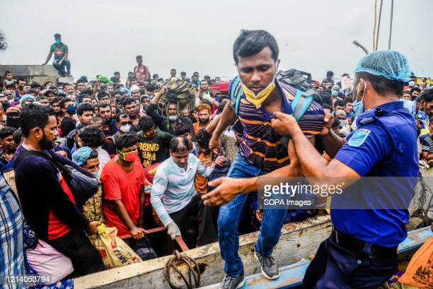 Worker, helps migrants on to the ferry to travel home for Eid al-Fitr amid Coronavirus crisis. Migrants flock at the Shimulia-Kathalbari ferry...