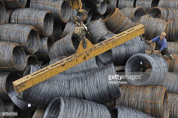 A worker helps to lift rolls of steel at a steel product market on May 15 2009 in Shenyang of Liaoning Province China According to the National...