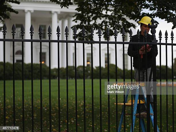 A worker helps with the restoration of the fence in front of White House October 23 2014 in Washington DC Last evening Dominic Adesanya of Bel Air...