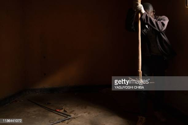 A worker hits a floor with a pickax to locate a pit which was used as mass grave during 1994 Rwandan genocide and hidden under a house is seen in...