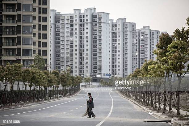 A worker holding a broom crosses a road in front of residential buildings in the Jiading district of Shanghai China on Monday April 11 2016 China's...