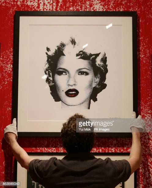 Worker holding Banksy's portrait of Kate Moss at a press preview for the exhibition Banksy: The Unauthorised Retrospective, curated by Steve...