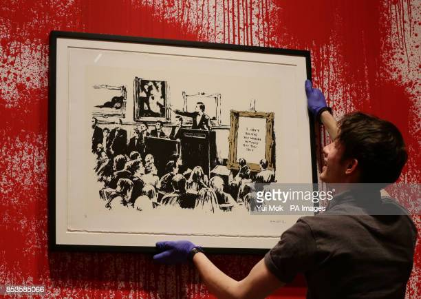 Worker holding Banksy's print 'Morons' at a press preview for the exhibition Banksy: The Unauthorised Retrospective, curated by Steve Lazarides, at...