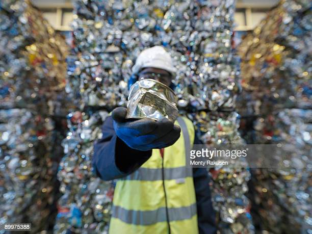 Worker Holding Can In Recycle Plant