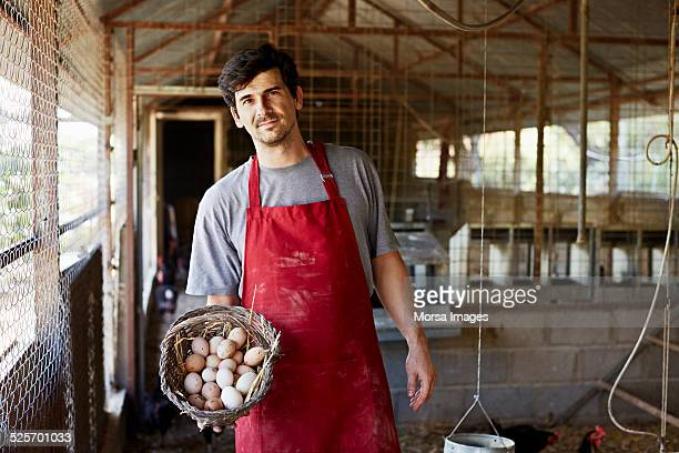 Worker holding egg basket at poultry farm