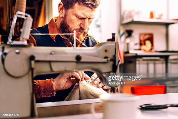 worker holding fabric at sewing table in workshop - sewing machine stock pictures, royalty-free photos & images