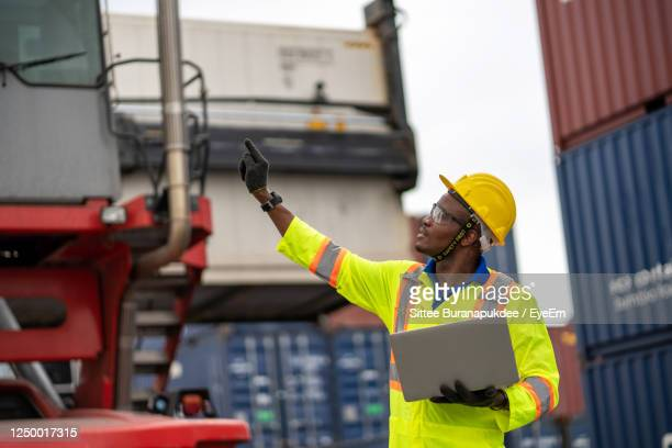 worker holding laptop with hand raised standing at dock - arms raised stock pictures, royalty-free photos & images