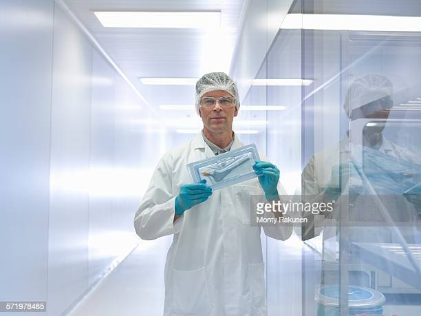 Worker holding orthopaedic hip stem replacement in clean room, portrait