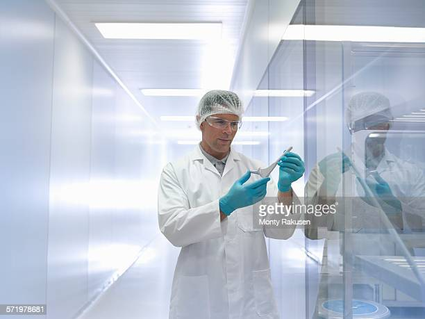 Worker holding orthopaedic hip stem replacement in clean room