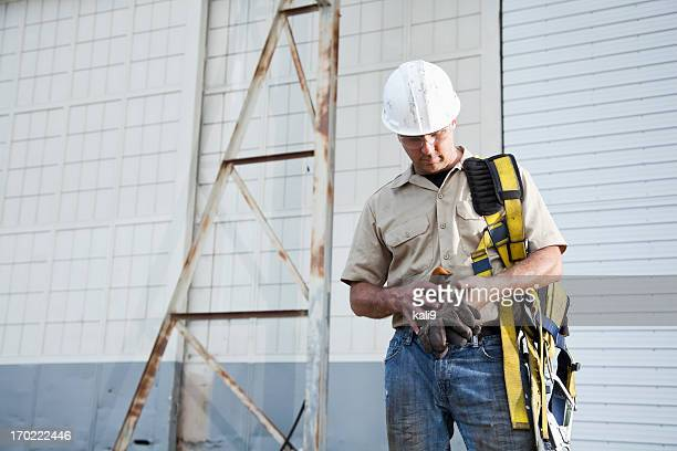 worker holding safety harness - safety harness stock photos and pictures