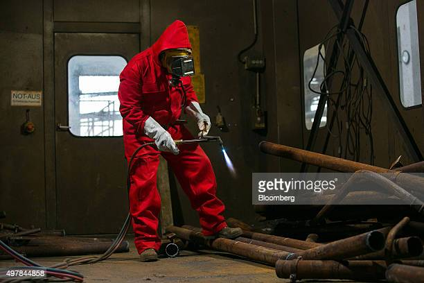 A worker holds a blowtorch during thermal cutting of metal pipework in the warm workshop as decommissioning operations continue at Lubmin nuclear...