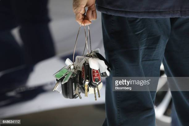 A worker holds a bundle of Alfa Romeo keys ahead of the 87th Geneva International Motor Show in Geneva Switzerland on Monday March 6 2017 The show...