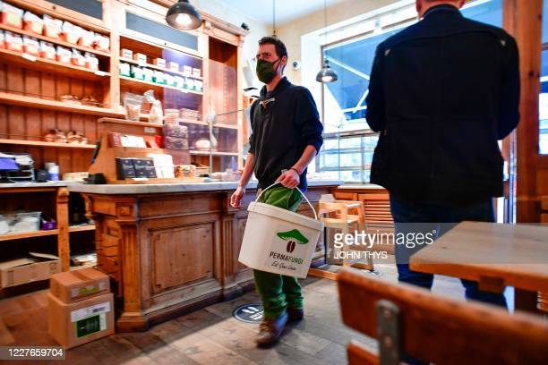 A worker holds a container as he prepares to collect coffee grounds from a shop in Brussels on July 15 for the company Permafungi which recycles...