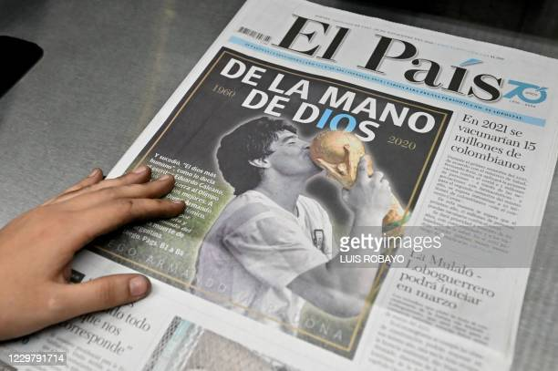 Worker holds a copy of the El Pais de Cali newspaper with a photo of late Argentinian football legend Diego Maradona on the front page, early on...