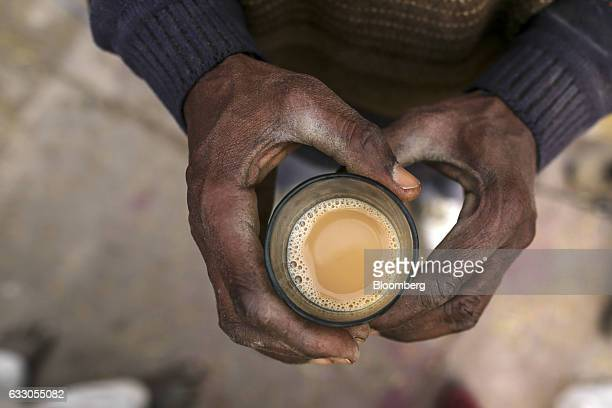 A worker holds a glass of chai while taking a break at an Agricultural Produce Market Committee wholesale market in Jalandhar Punjab India on...