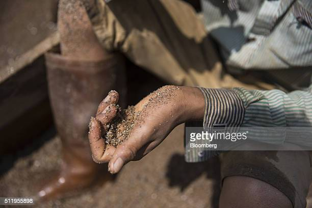 A worker holds a handful of sand on the banks of a river at a sand dredging site near Kengtung Shan State Myanmar on Thursday Feb 18 2016 The...