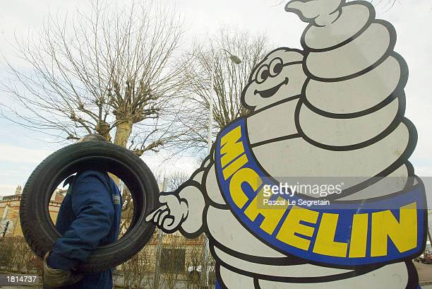 A worker holds a Michelin tire near the Michelin Man logo February 25 2003 in Saint Germain en Laye outside of Paris The French tire maker announced...