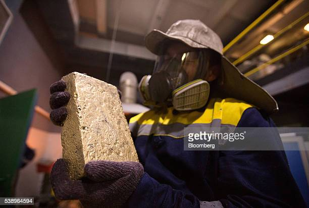 A worker holds a newly cast 175 kilogram gold bar following cleaning at the Suzdal gold mine operated by Nordgold NV in Semey Kazakhstan on Tuesday...