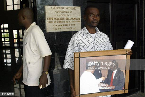 A worker holds a photograph of an exchange of gifts between Nigeria Labour Congress President Adams Oshiomhole and Deputy Senate President Ibrahim...