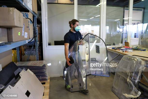 A worker holds a plexiglass divider to be installed inside cars at Plexismart Srl in Guidonia close to Rome Italy on Wednesday May 20 2020...