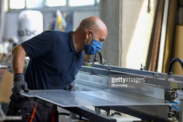 A worker holds a plexiglass screen while warming it at Plexismart Srl in Guidonia close to Rome Italy on Wednesday May 20 2020 Floortoceiling...