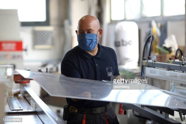 A worker holds a plexiglass sheet after warming it at Plexismart Srl in Guidonia close to Rome Italy on Wednesday May 20 2020 Floortoceiling...
