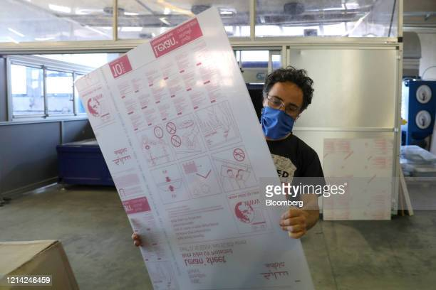 A worker holds a plexiglass sheet at Plexismart Srl in Guidonia close to Rome Italy on Wednesday May 20 2020 Floortoceiling plexiglass dividers could...