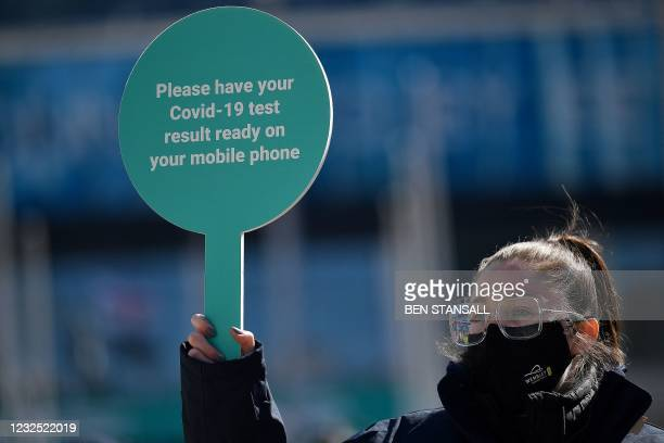 Worker holds a sign asking fans to prepare to show their negative test result for Covid-19, as they arrive at Wembley Stadium to watch the English...