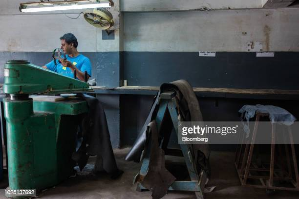 A worker holds a template while cutting leather patterns for safety shoes on a desk at the Lyra Ltd factory in Karachi Pakistan on Thursday Aug 16...