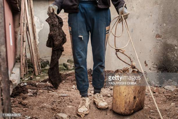 TOPSHOT A worker holds a victim's cloth recovered on April 9 2019 from a pit which was used as a mass grave during the 1994 Rwandan genocide and...
