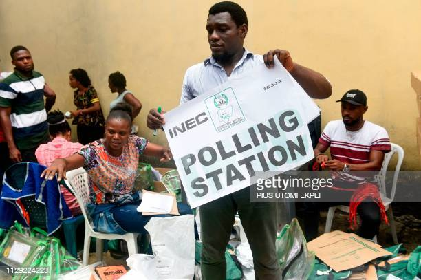 A worker holds an election poster to be displayed at a polling station at the Independent National Electoral Commission central office in Port...