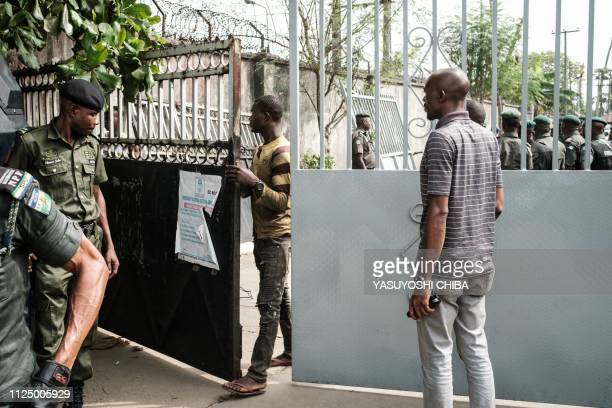 A worker holds and replaces a main gate at the local office of the Independent National Electoral Commission as Nigerian police officers gather in...