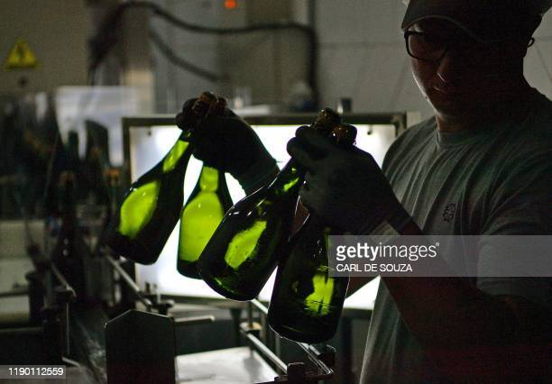 Worker holds bottles of sparkling wine at the Familia Geisse vineyard in Pinto Bandeira, Rio Grande do Sul state, Brazil, on December 3, 2019. -...