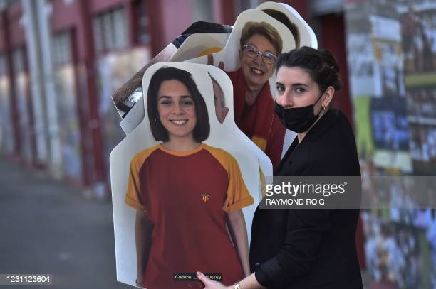 Worker holds cardboard cutouts of rugby supporters ready to be set up in grandstand of the Aime Giral stadium ahead of the French Pro D2 rugby match...
