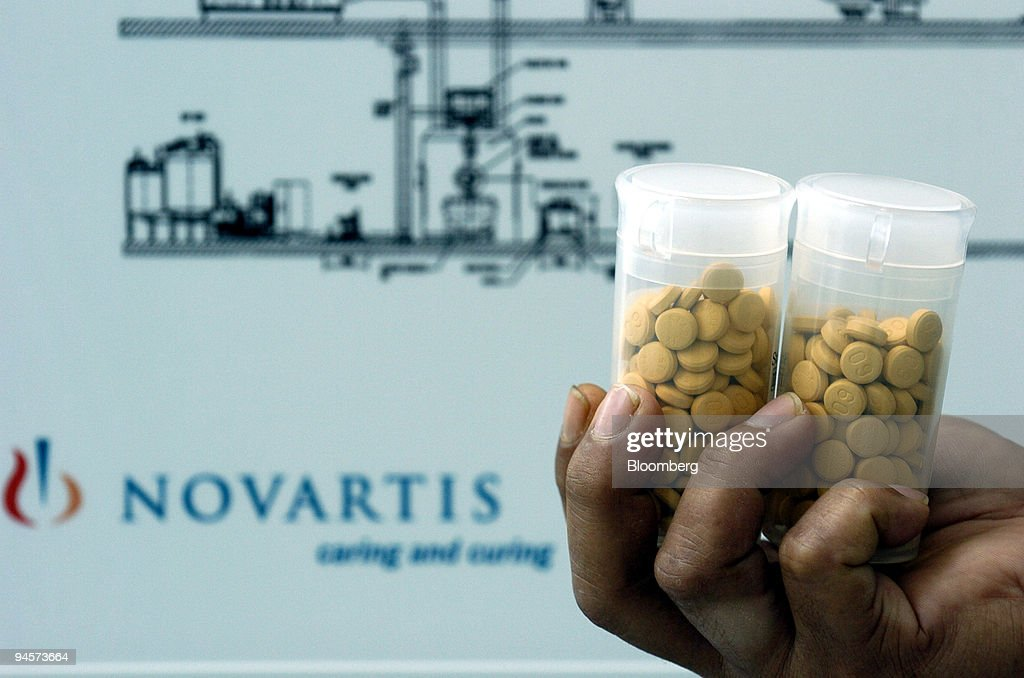 A worker holds containers of test tablets made in the Novart : News Photo