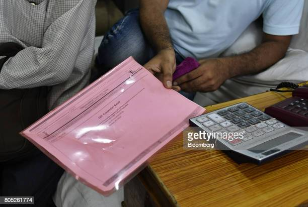 A worker holds his GST papers in his store at a wholesale market in the Old Delhi area of Delhi India on Saturday July 1 2017 The new goods and...