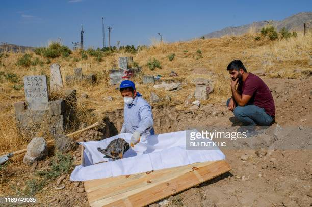 A worker holds the covered head of a corpse of a 15yearold boy who died in 1997 in an accident in Hasankeyf as his 28yearold brother Fatih looks on...
