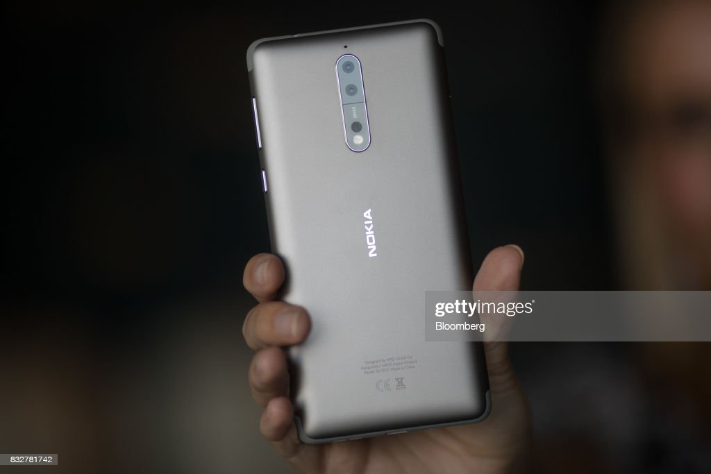 A worker holds the Nokia 8 smartphone, designed by HMD Global Oy, ahead of its official unveiling in London, U.K., on Tuesday, Aug. 15, 2017. The phone will feature a dual-sight photo and video function, in which images from the front and rear cameras will be displayed simultaneously on a split screen. Photographer: Simon Dawson/Bloomberg via Getty Images