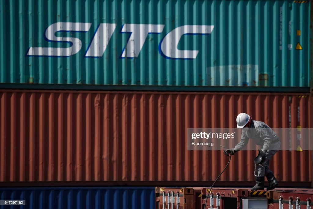 A worker holds tools while performing maintenance work on a container at a shipping terminal in Yokohama, Japan, on Monday, April 16, 2018. Japan and China held their first high-level economic dialogue in almost eight years on April 16 against a backdrop of trade threats from the U.S. Photographer: Akio Kon/Bloomberg via Getty Images