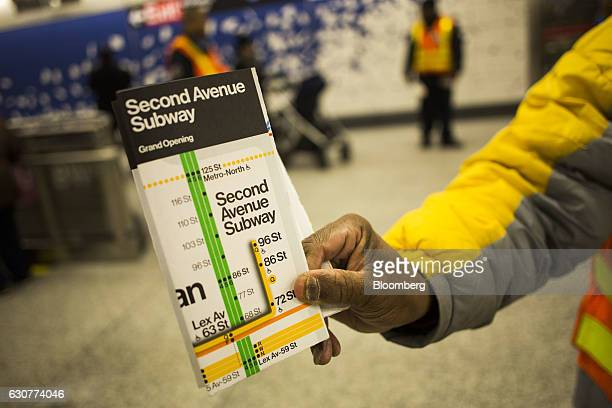 A worker holds up a map at a station on the newly opened Second Avenue subway line in New York US on Sunday Jan 1 2017 The first train departed the...