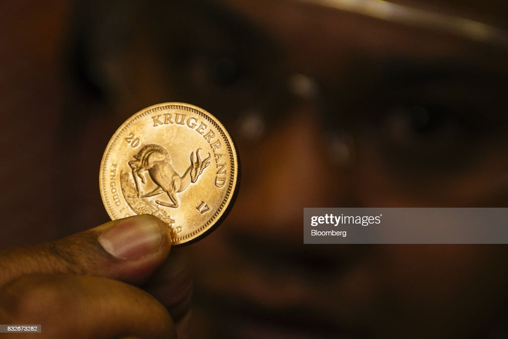A worker holds up a proofed krugerrand gold coin manufactured at the Rand Refinery Ltd. plant in Germiston, South Africa, on Wednesday, Aug. 16. 2017. Established by the Chamber of Mines of South Africa in 1920, Rand Refinery is the largest integrated single-site precious metals refining and smelting complex in the world, according to their website. Photographer: Waldo Swiegers/Bloomberg via Getty Images