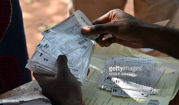 A worker holds voter registration cards during a distribution in Bangui on December 25 2015 ahead the country's presidential elections The transition...