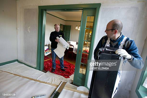 A worker holds wallpaper rolls on December 2 2011 during the restoration of the flat where Anne Frank lived with her family in Amsterdam before they...
