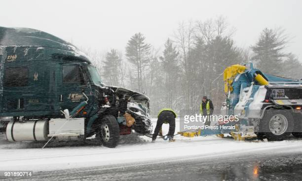 A worker hooks a tow truck to a tractor trailer that got stuck in the median of the Maine Turnpike in Wells on Tuesday March 13 2018