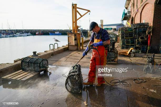 A worker hoses down lobster and crab pots on the quayside in the harbour in Scarborough UK on Tuesday June 2 2020 The threat of a nodeal Brexit is...