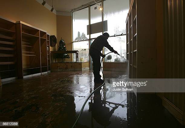 A worker hoses off shelves inside a cooking supply store January 2 2006 in San Anselmo California Northern California has been inundated by heavy...