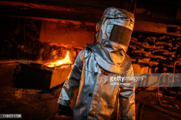 A worker in a fire suit seen supervising the flow of hot liquid metal as it flows from a furnace at the plant Production of matte nickel at the PT...