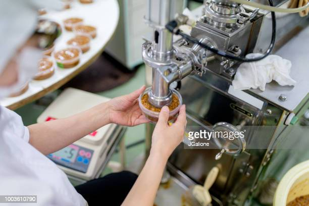 worker in a food processing factory packaging food - rice food staple stock pictures, royalty-free photos & images